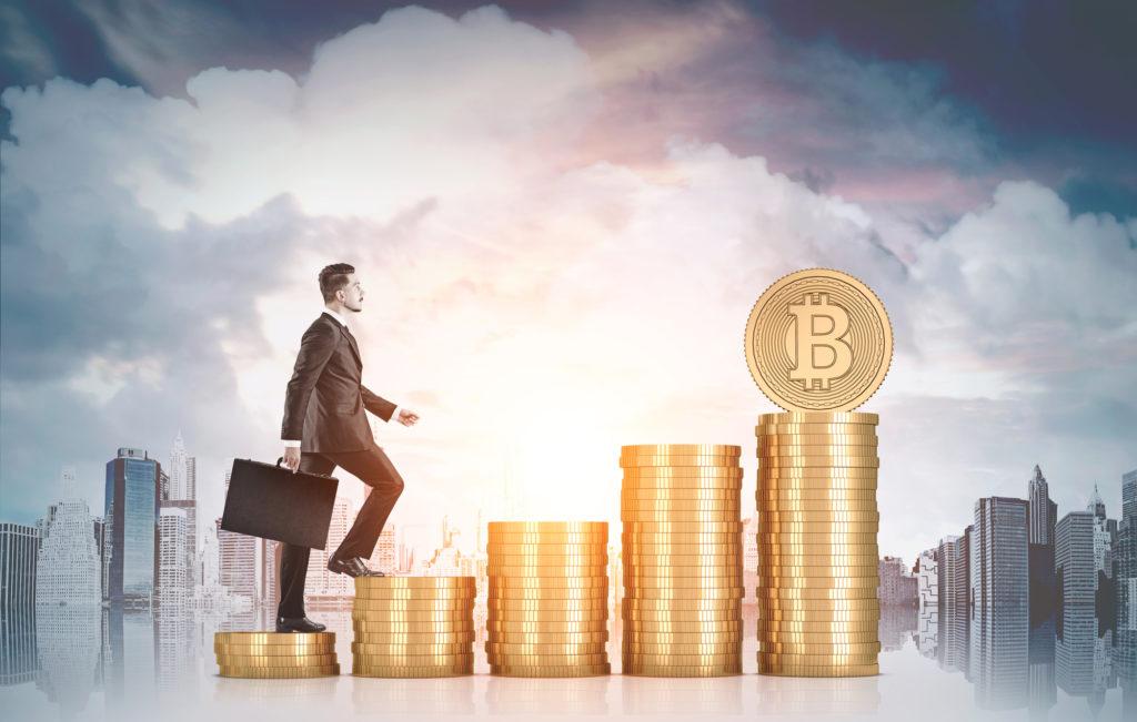 Businessman climbing stacks of bitcoins, city